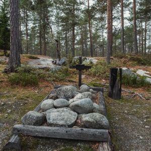 Kiviä maassa aseteltuna puisen kehikon sisään, risti, taustalla metsäistä maisemaa, pohjoisgrönlantilainen hauta