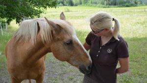 Pia Kulla tillsammans med en häst som buffar på hennes mage.