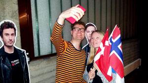 Niklas Ollila och Sonja Bäckman med danska och norska flaggor tar selfie under UMK 2019 med pappfigruen Darude. Pappfiguren Sebastian Rejman får inte var med på deras bild.