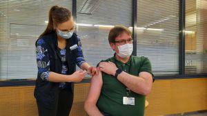 TyöPlussasta Mirjami Myllymäki antaa koronarokotteen infektioylilääkäri Marko Rahkosen käsivarteen