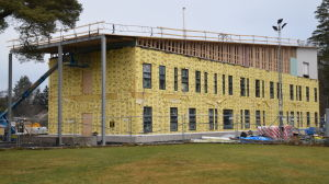 Ett två våningar stort hus byggs, ställningar på taket, gul isolering på väggarna.
