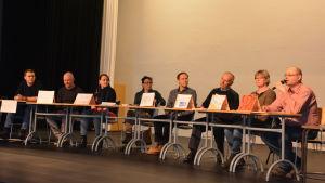 Politiker i Hangö sitter i valdebatt i Hankoniemen lukio. Theo Sjöblom (SFP), Sven Sundström (Hangö 2016), Pirkko Heinänen (Saml), Mira Haahti (FKP), Timo Sarojärvi (Grön), Pekka Tuunanen (Sannf), Birgitta Gran (VF) och Tom Rönnblad (SDP).