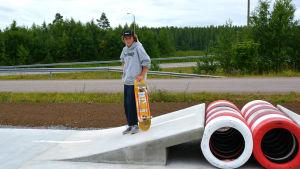 Pojke står på liten betongramp och håller i skateboard