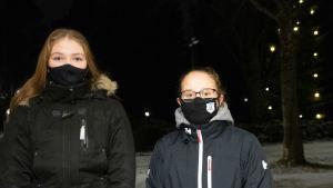 Två flickor står i mörker med munskydd på sid.
