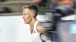 Topi Raitanen springer bakom en kameraman.