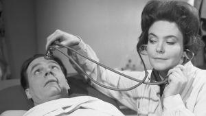 Lääkäri (Tiina Rinne) kuuntelee stetoskoopilla potilaan (Tommi RInne) otsaa Iskelmäkarusellissa 1964.