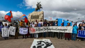 """Demonstranter i Ulan Bator håller upp banderoller med texten """"Rädda det mongoliska språket""""."""