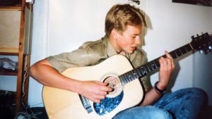Programledaren Mårten Svartström som ung, spelar på sin gitarr.