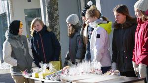 Ett gäng med ungdomar står och säljer saker vid ett torgstånd.