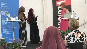 Två kvinnor i hijab intervjuas av en tredje kvinna på en mindre scen.