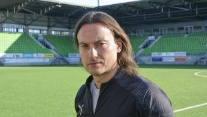 Christian Sund, tränare för VPS, tittar in i kameran. Sandviken stadion i bakgrunden.