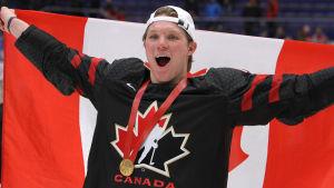 Ty Dellandrea håller upp den kanadensiska flaggan bakom ryggen och jublar.