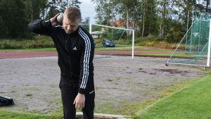 Mikael Kock håller en kulstötnings kula mot nacken, redo att stöta.
