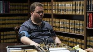 Richard Jewell (Paul Walter Hauser) sitter vid ett bord och tar en lögndetektortest. niskor.