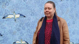 Eija Lang framför en blå vägg.