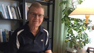 En äldre man, psykolog, som sitter vid ett bord.