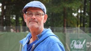 Profilbild på en glasögonprydd man i blå keps och blå munkjacka på en tennisbana.