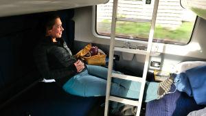 Sanna-Mari Kunttu, en kvinna med mörkt hår och svart tröja, sitter i en tågkupé och tittar ut genom fönstret.