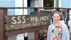kvinna stor framför restaurangskylt.