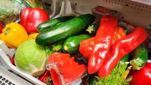 Gurka, paprika och andra grönsaker framställda i en butik.