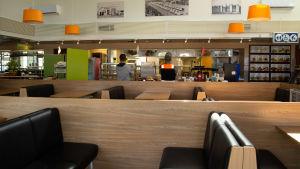 En tom matsal, ingen sitter vid borden. Två män står med två meters avstånd och tittar på menyn.