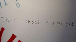 poikien wcn seinäkirjoitus This school is a prison!