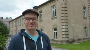 Daniel Saarinen framför gamla huvudbyggnaden på Ekåsen.