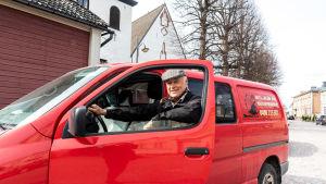 Kalle Augustson vid sin röda bil.