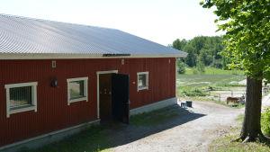 En lång, låg byggnad målad i rött och åkrar och en häst som skymtar i bakgrunden.