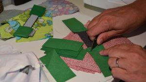 Tygbitar i grönt och rött ligger på sybordet. Den ena handen håller i en grön tygbit och den andra handen klipper av en sytråd.