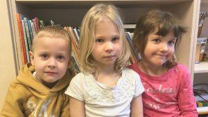 Tre barn i dagisåldern framför en bokhylla med barnböcker.