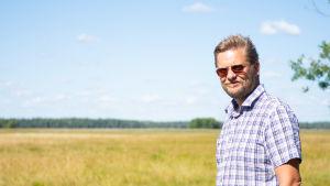 Man i rutig skjorta och solglasögon står vid en äng och ler, ljusblå himmel med ett litet vitt moln.