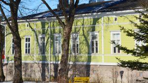 Bild på Strömborska skolan utifrån med grönt hus.