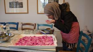 Ayaa Sheikh Jalal doftar på rosenblad som ska användas i honung.
