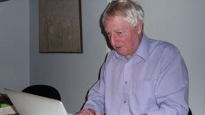 Ulf Persson sitter vid sin dator och skriver.