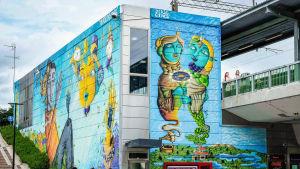 Myyrmäen juna-aseman julkisivu, värikäs seinämaalaus.