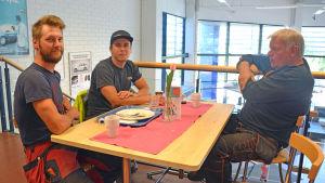 Tre män som sitter vid ett bord på en lunchrestaurang.