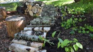 Blomplantering mellan en sluttning ochd en mur av ved