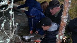 Utomhuspedagogen Patrik Berghäll lär elever att göra upp eld under en stor sten