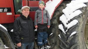 En man med blå jacka och grå keps står framför en stor röd traktor (skogstraktor). På traktorns trappsteg står en sexårig pojke. De ser in i kameran. Snö på traktorhjulet.