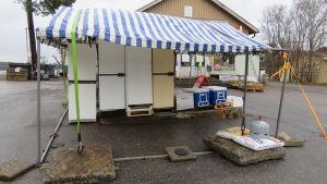 Ett tält i blå-vitt plast som står utanför en matbutik. Inga ytterväggar. Innanför tältet finns kylskåp och frysar.