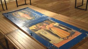En dörr ligger utställd i ett museum. Dörren är blå och visar ett tjurhuvud och en kvinna och ett barn. Dörren har målats av Ilmari Wirkkala.