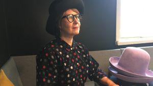 Designern Hanna Sarén sitter på ett café med hattar på bordet.