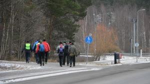 En grupp människor promenerar på en lättrafikled.