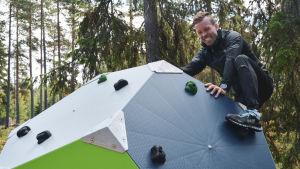 Joakim Träskelin klättrar på klätterkub i skogsmiljö.