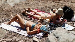 Två kvinnor ligger på handdukar på en strand och solar i bikinis.