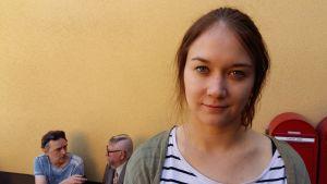 Emma Heino. I bakgrunden blir Kari Väänänen (Aulis Homelius) intervjuad.