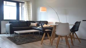 Ett vardagsrum med en soffa och ett bord. Till höger står ett köksbord med fyra stolar.