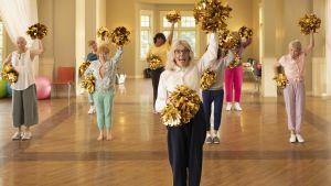 Damerna på äldreboendet övar hejarklascksrörelserna under ledning av Diane Keaton.