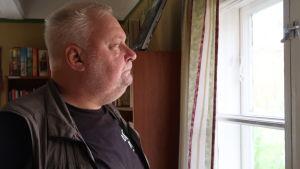 Tomy Wass tittar ut genom ett fönster och ser allvarlig ut.